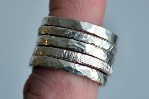 Silver stacking rings are available in full and half sizes 3-12. Each ring is hand hammered into textures resembling rocks and bark.